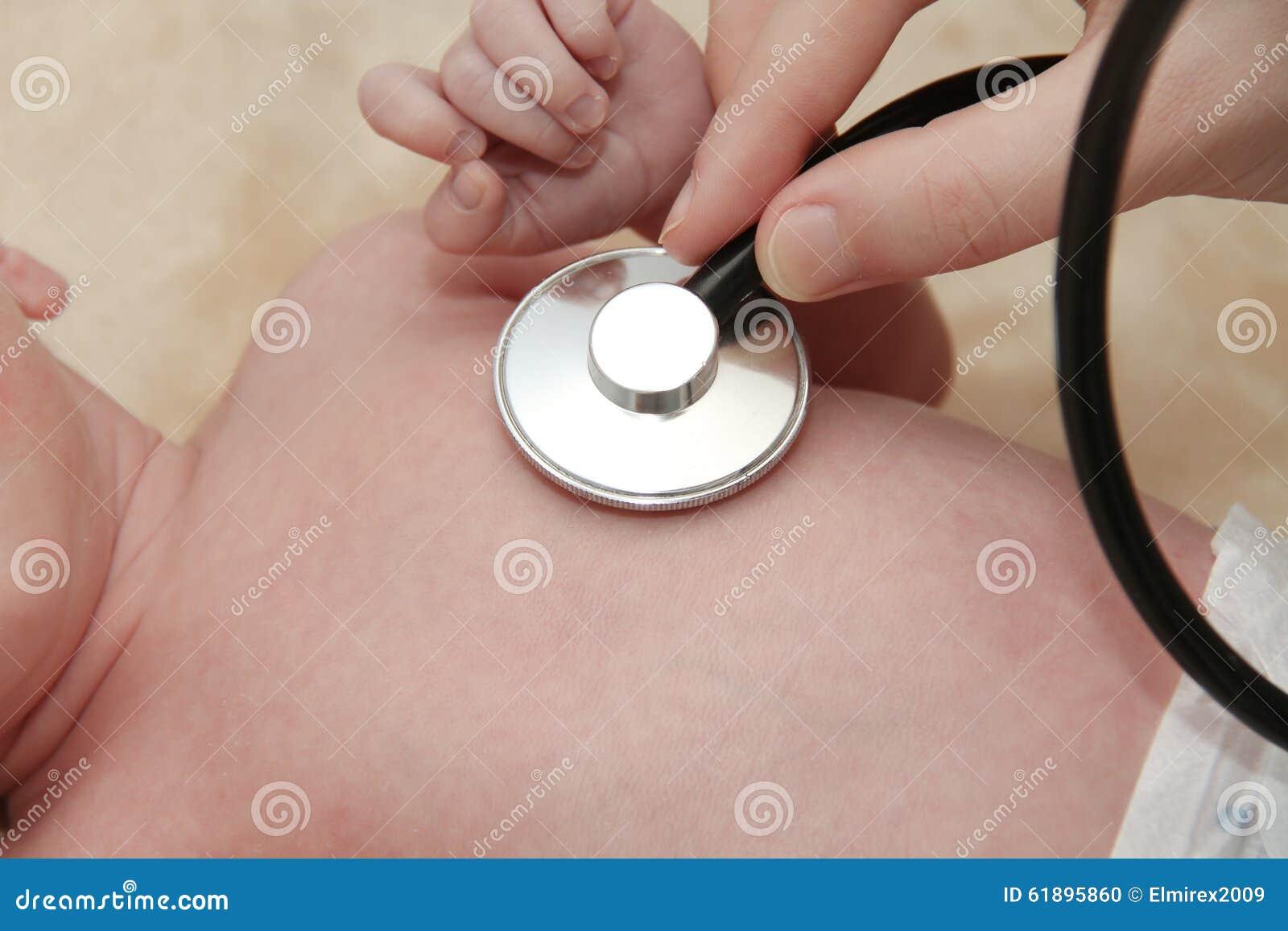 El bebé masculino consigue un examen del pulmón de una enfermera con el estetoscopio