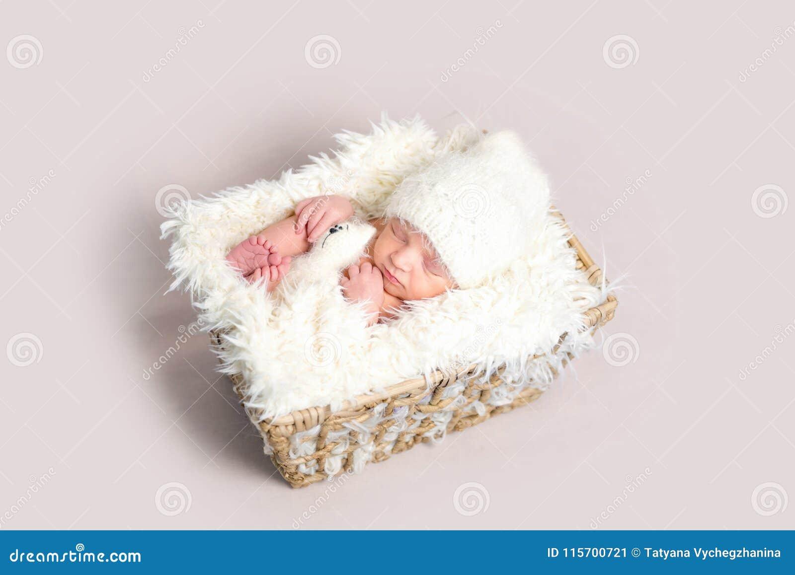 El bebé recién nacido dormido encendido apoya con las piernas encrespadas para arriba