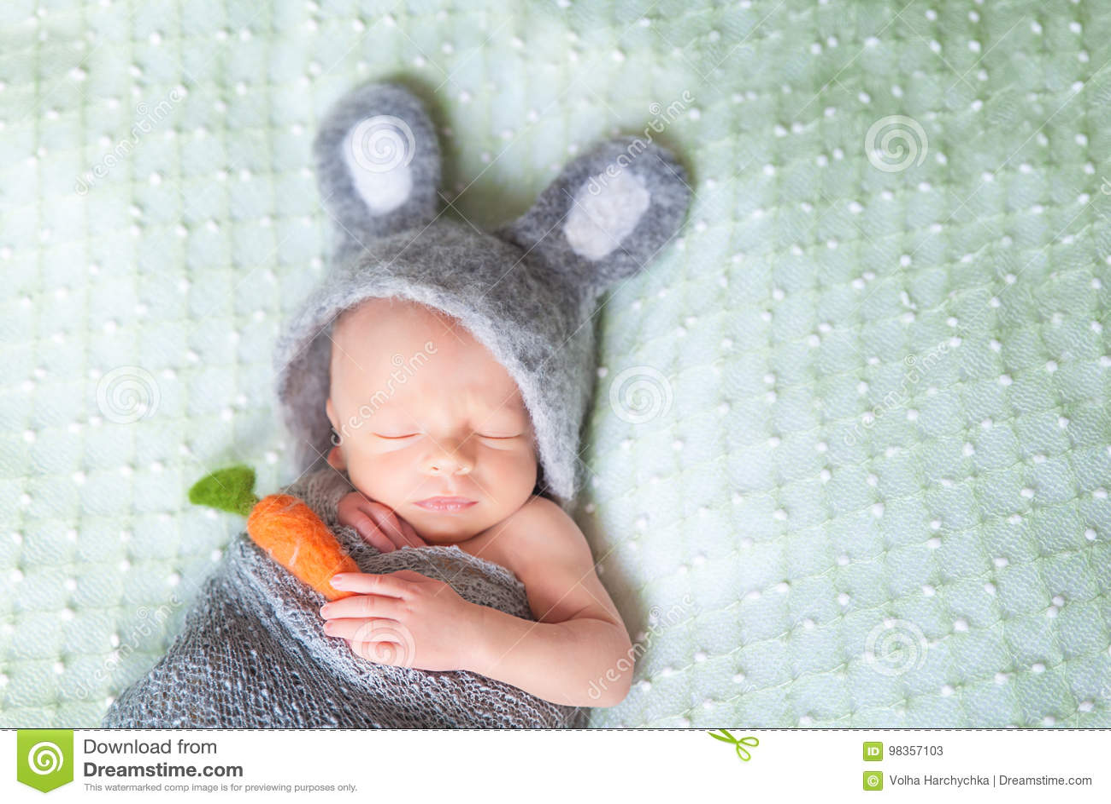 El bebé recién nacido durmiente lindo se vistió como el conejito de pascua
