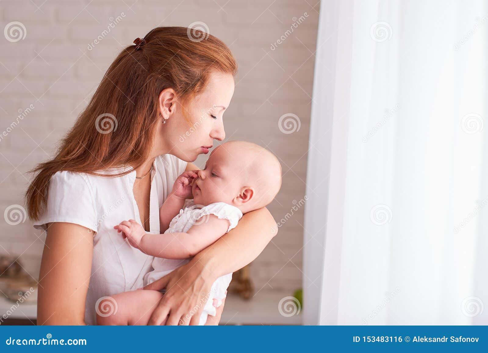 El beb? en los brazos de la madre amamanta La momia introduce al ni?o con el espacio del texto libre Copie el espacio
