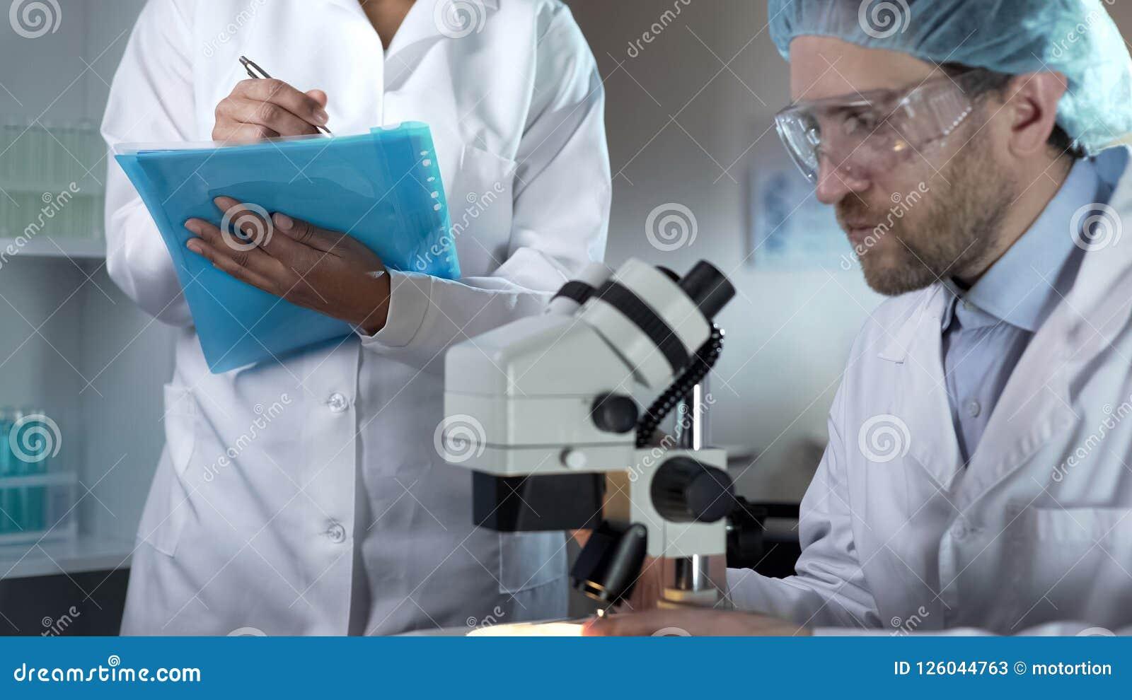 El biólogo que estudia muestras debajo del microscopio, ayudante que anota comenta