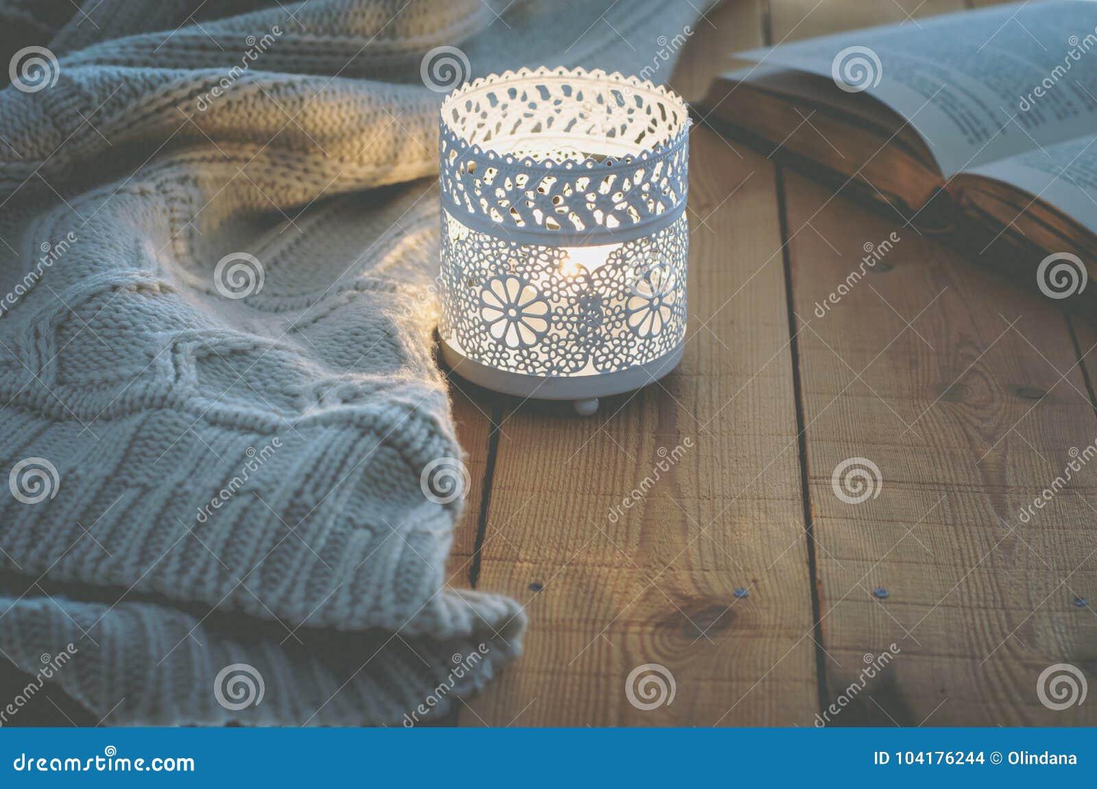 El blanco de la vela del Lit hizo punto el libro abierto del suéter en la tabla de madera del tablón por la ventana Invierno acog