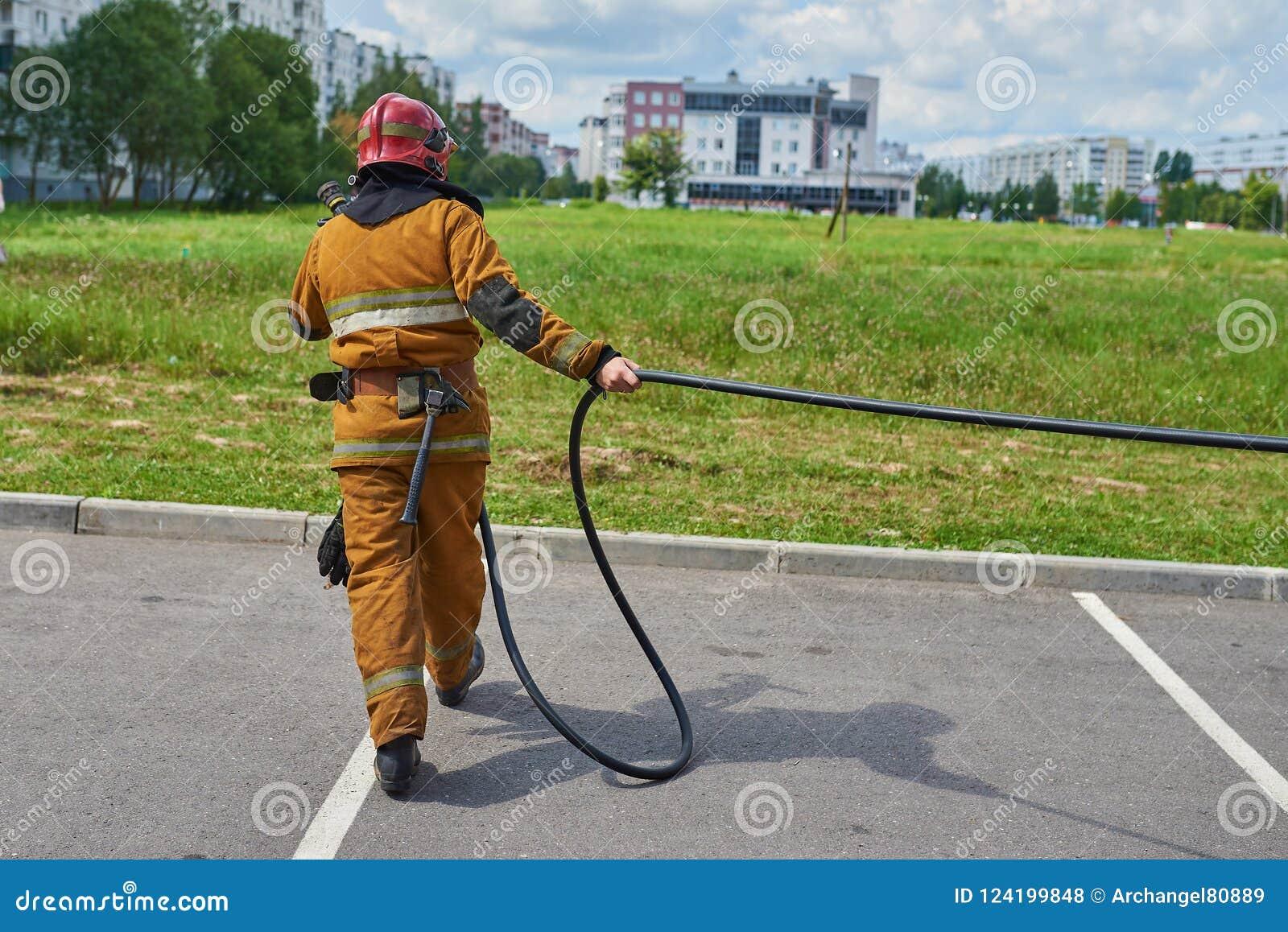 El bombero de sexo masculino tira de la manguera
