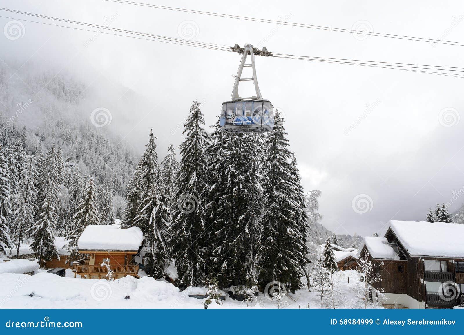 El bosque nevado y los chalets alpinos en un ferrocarril aéreo