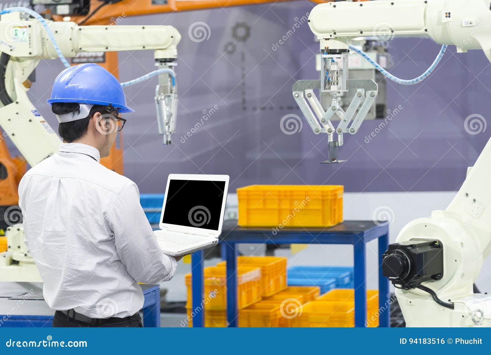 El brazo del robot del control del ingeniero industrial