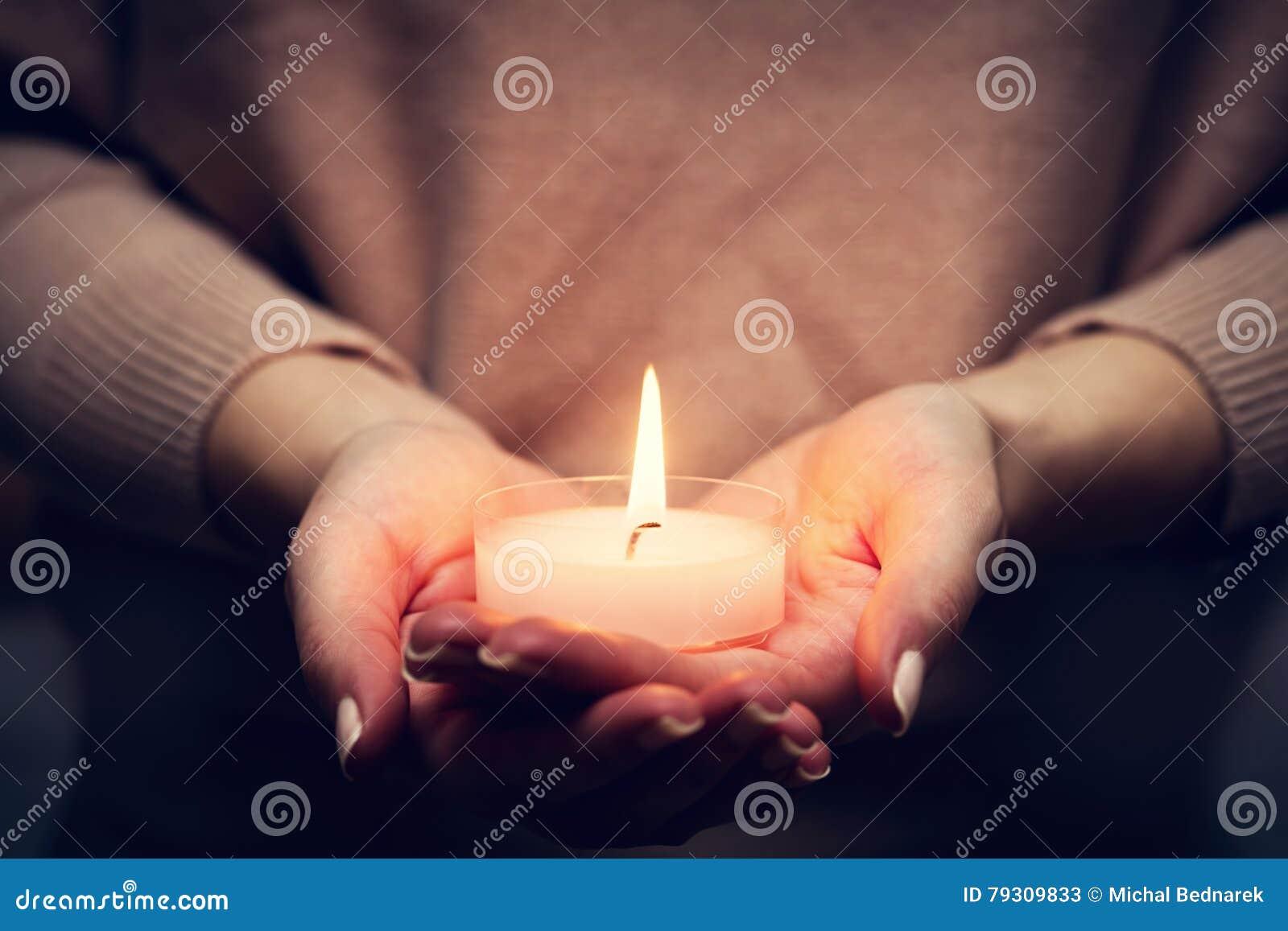 El brillar intensamente ligero de la vela en el woman& x27; manos de s Rogación, fe, religión