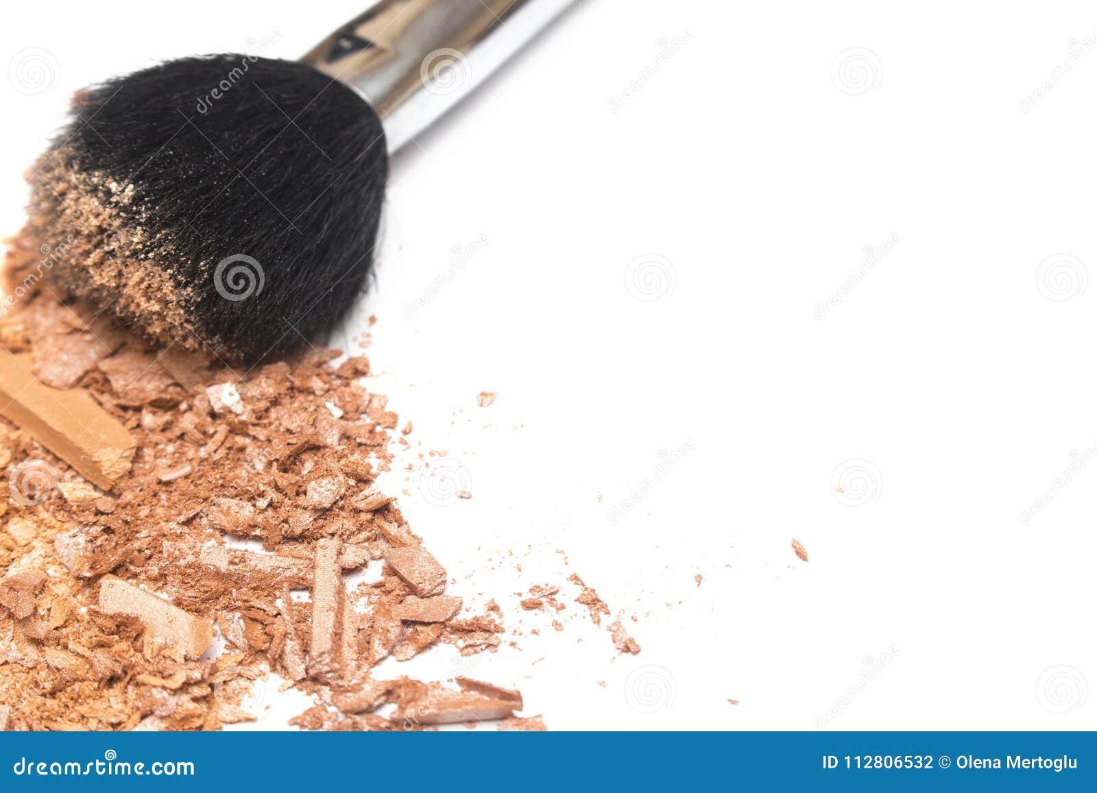 El bronzer machacado del polvo se ruboriza y pulveriza el cepillo en el fondo blanco