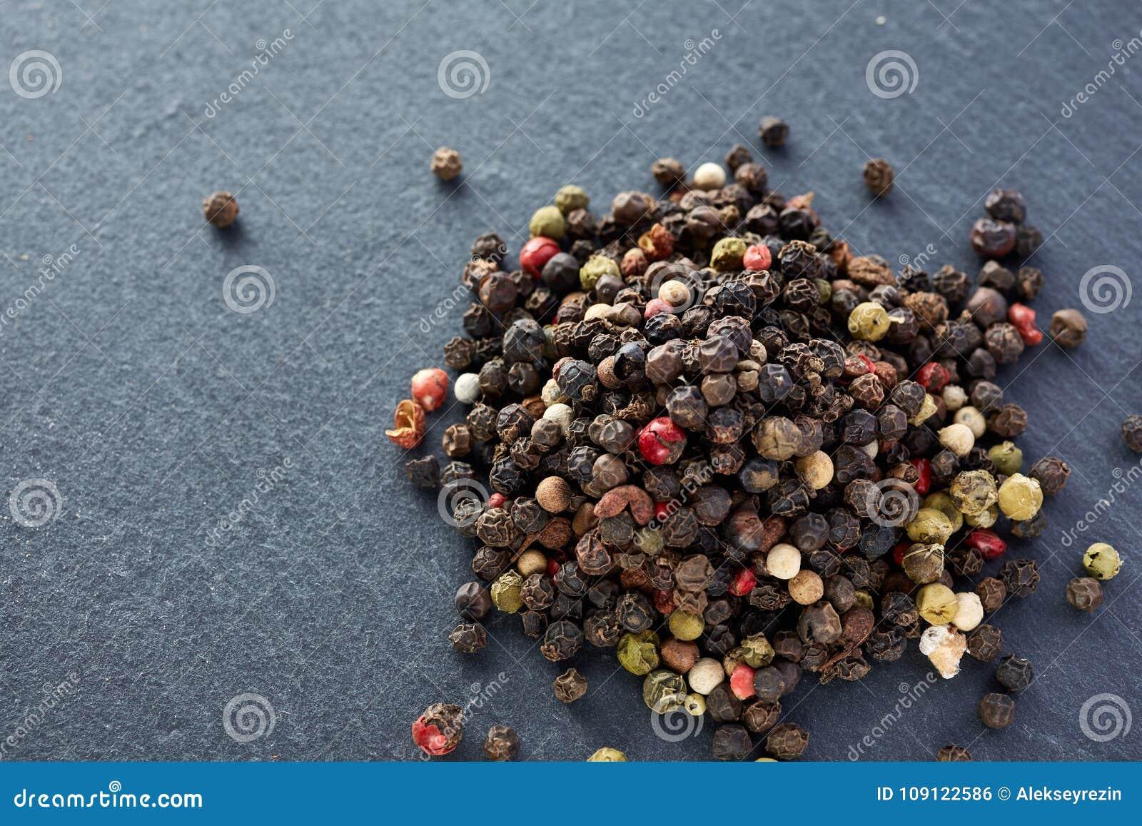 El bulto de diversas semillas de los granos de pimienta de la pimienta se mezcla en piedra oscura