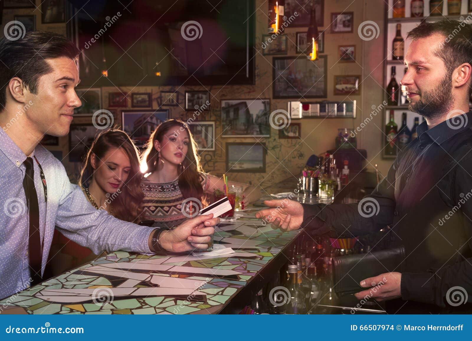 El caballero invita a sus amigos y paga con la tarjeta de crédito en el co