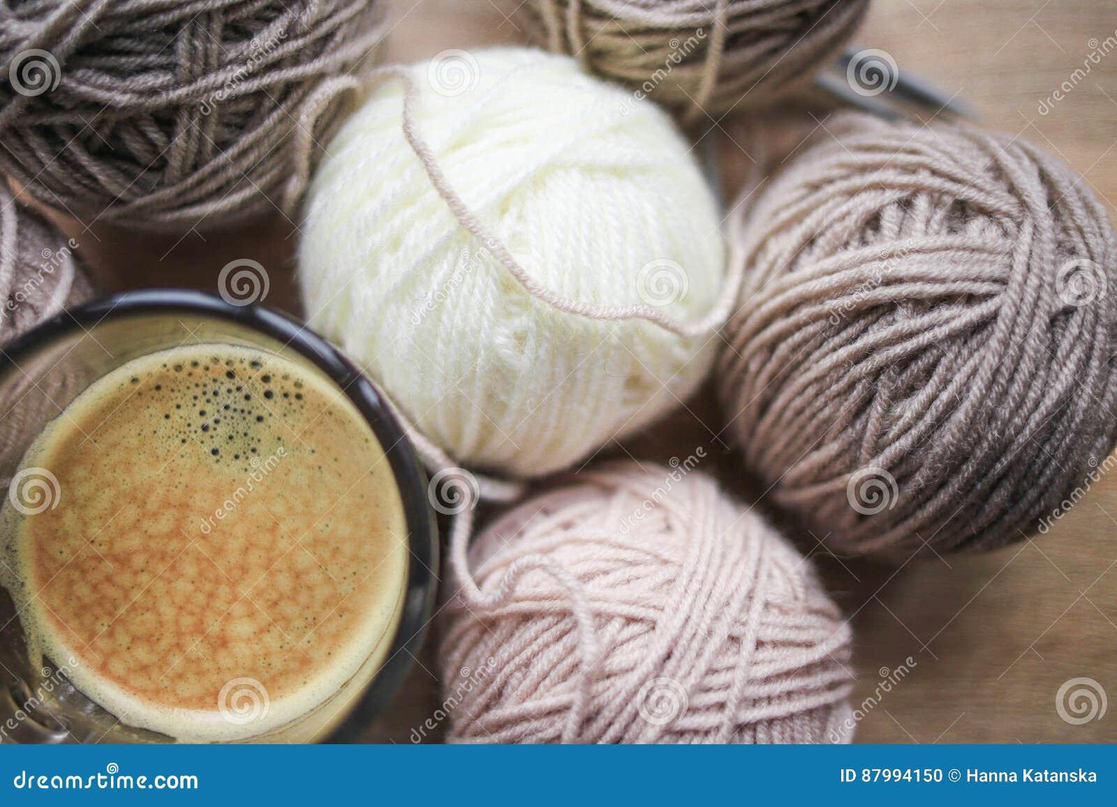 El café, el hilado de las agujas que hace punto, beige y blanco están en la tabla