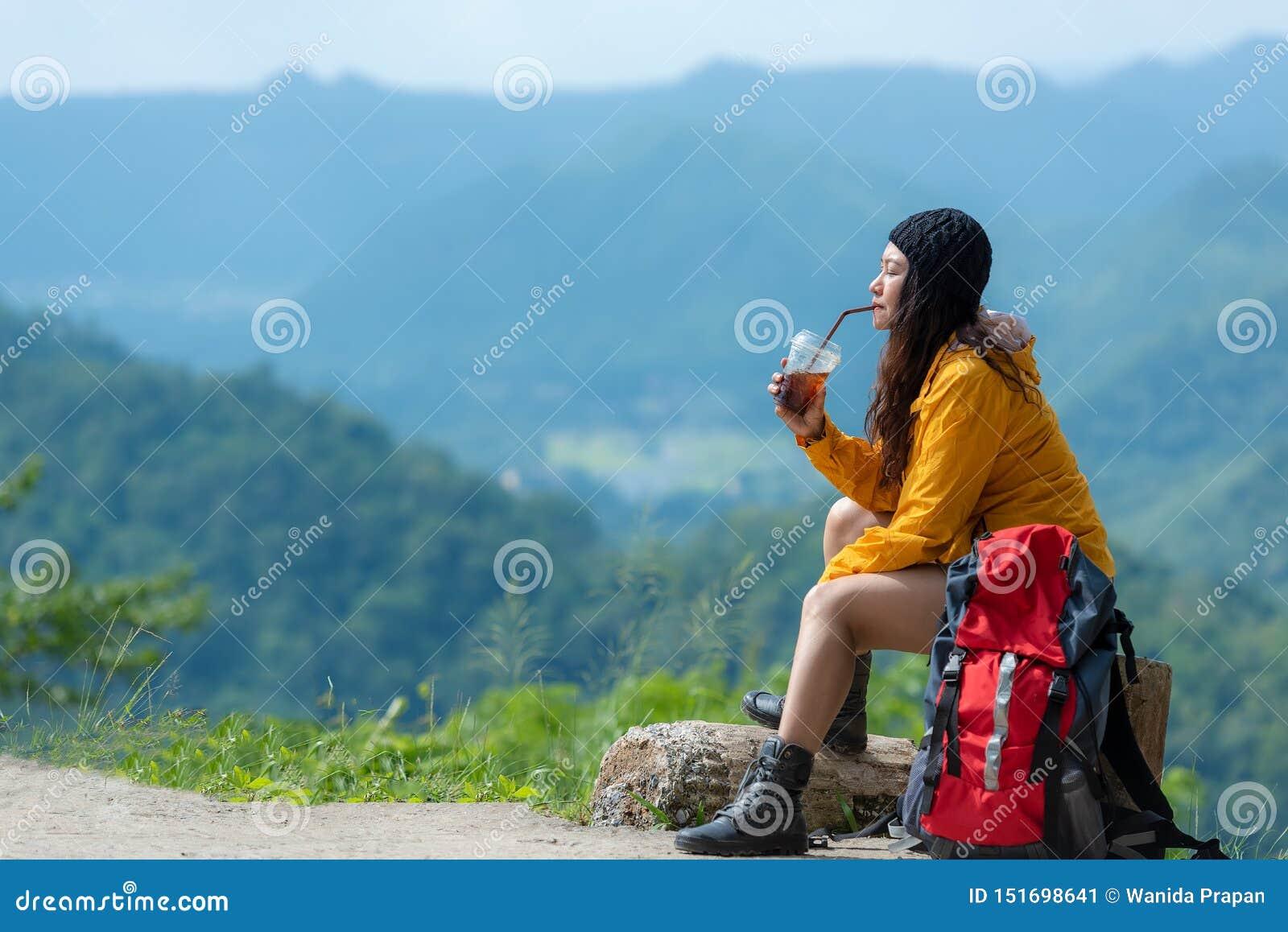 El café que se sienta y de consumición de la mujer asiática del caminante para se relaja y descansa sobre la montaña Mochila feme