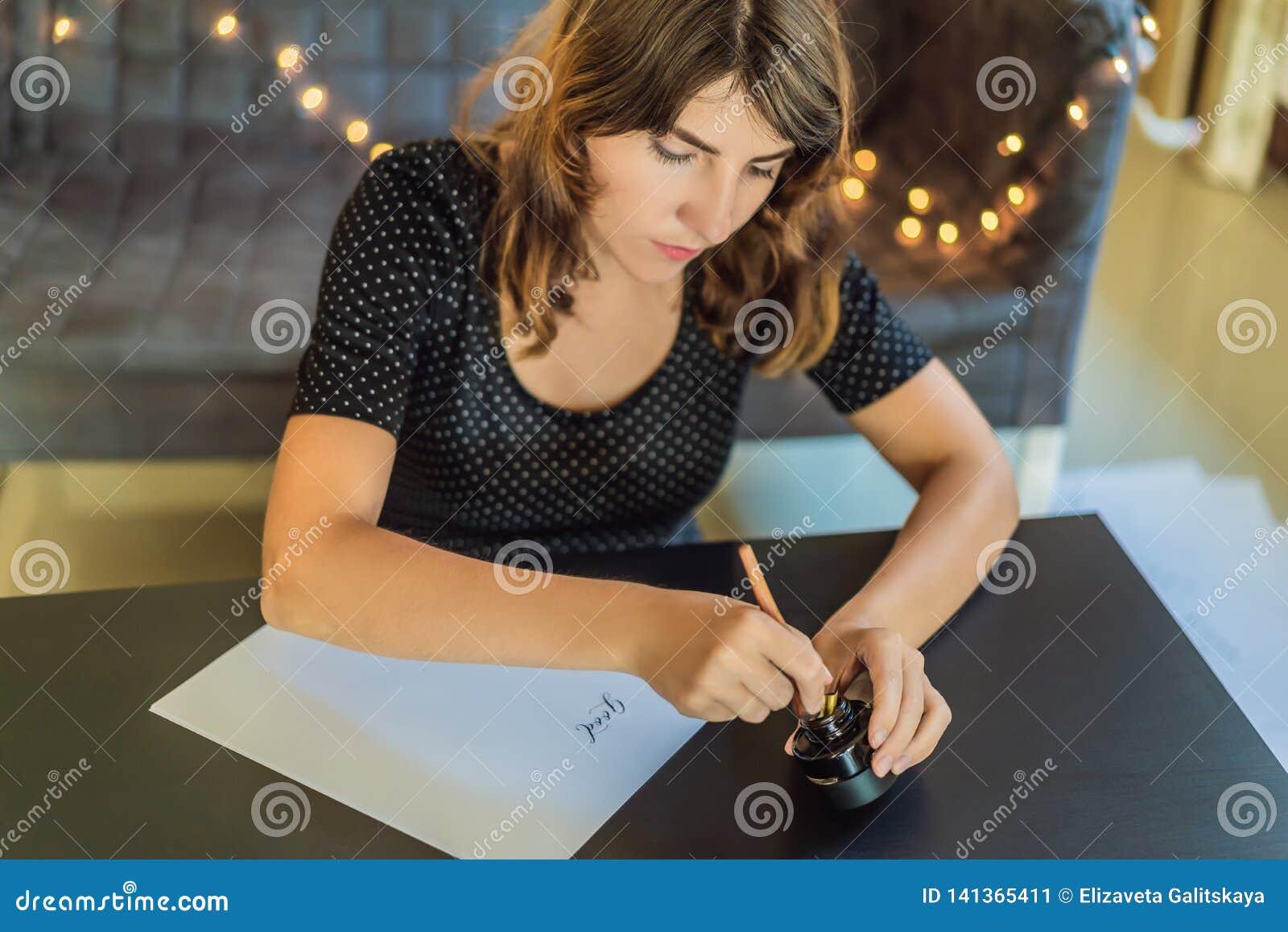 El calígrafo Young Woman escribe frase en el Libro Blanco Buenos días Inscripción de letras adornadas ornamentales