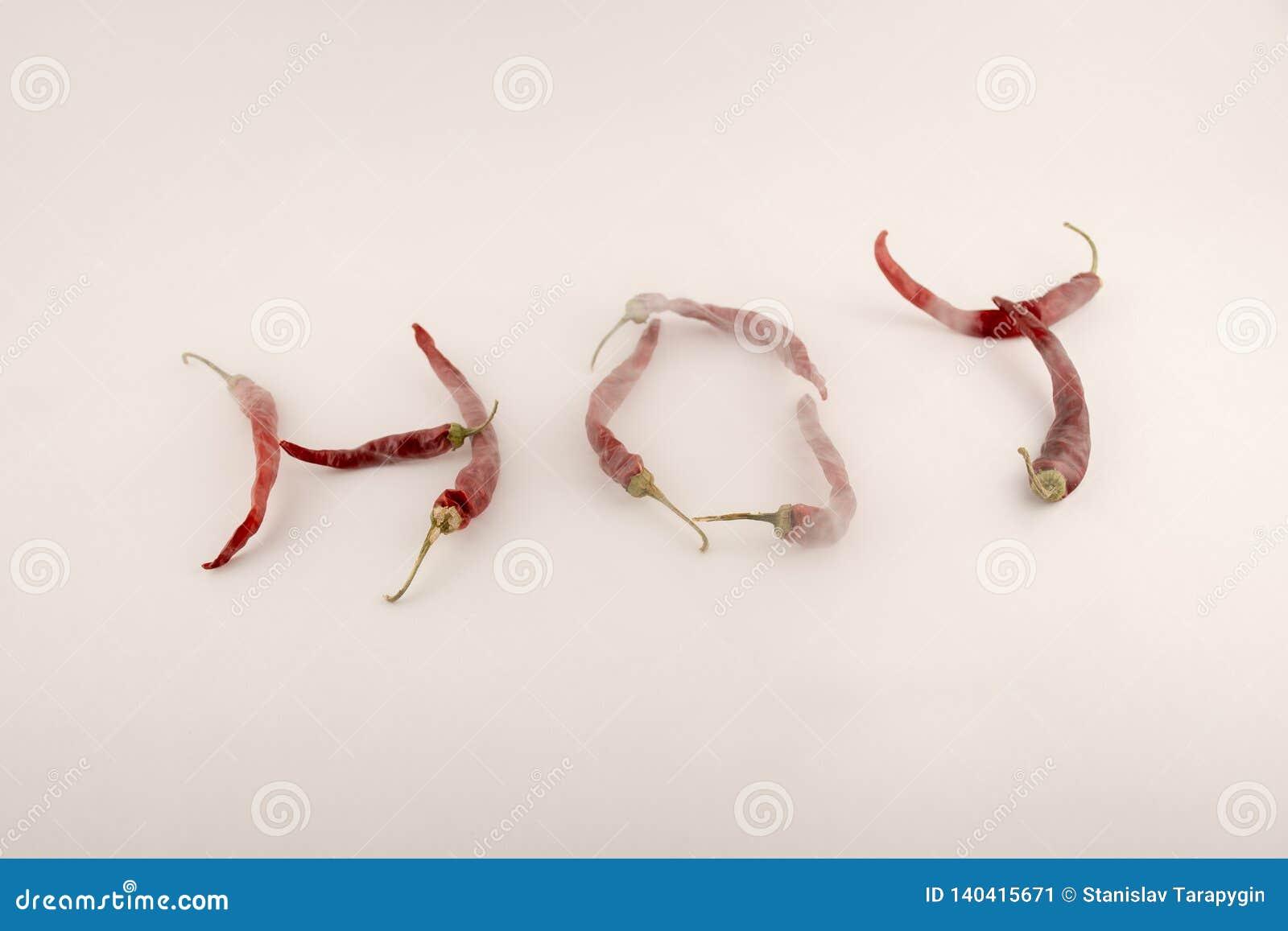 El caliente de la palabra construido de las pimientas de chile rojo con los troncos verdes en un fondo blanco