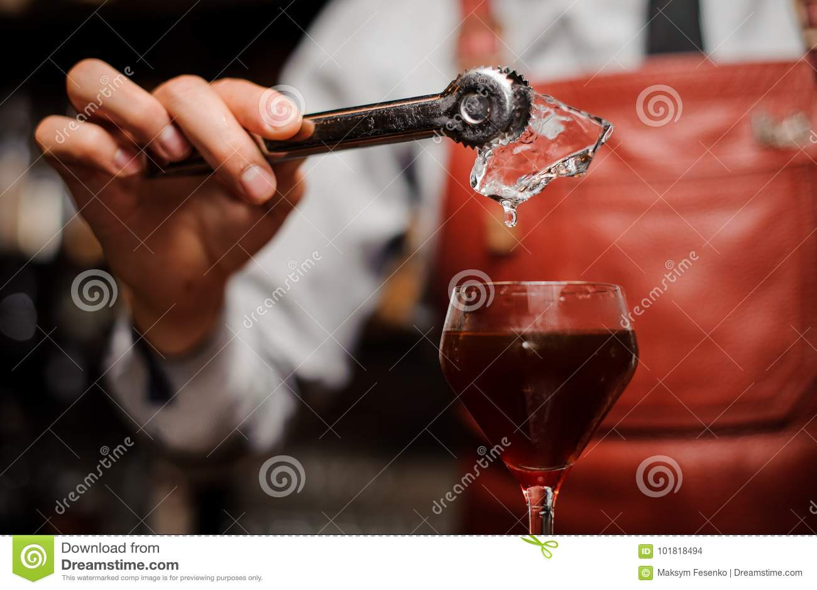 El camarero está poniendo un hielo en el coctail