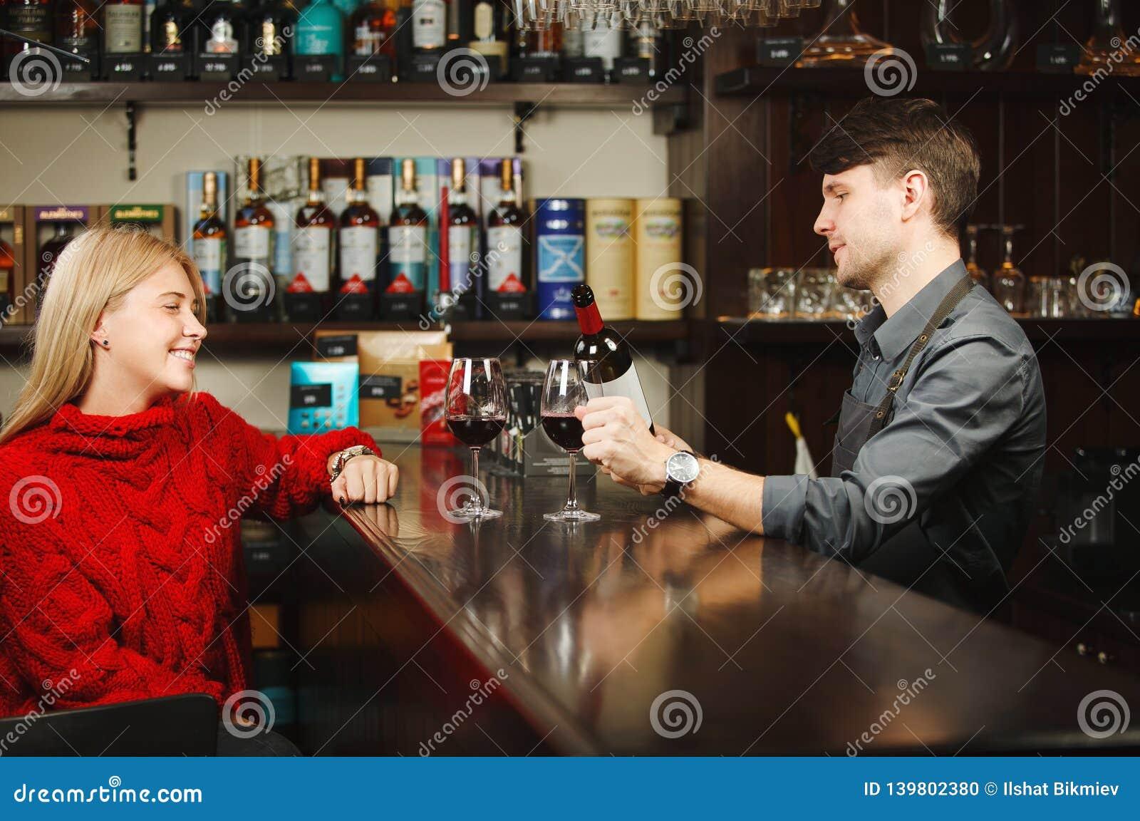 El camarero llena dos vidrios del vino rojo de la botella