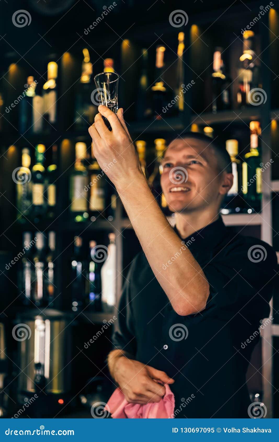 El camarero mira un cristal El camarero que limpia el vidrio en la barra