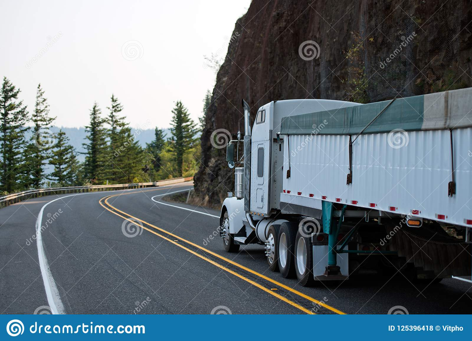 El camión grande del blanco del aparejo semi con bulto cubrió semi el funcionamiento del remolque