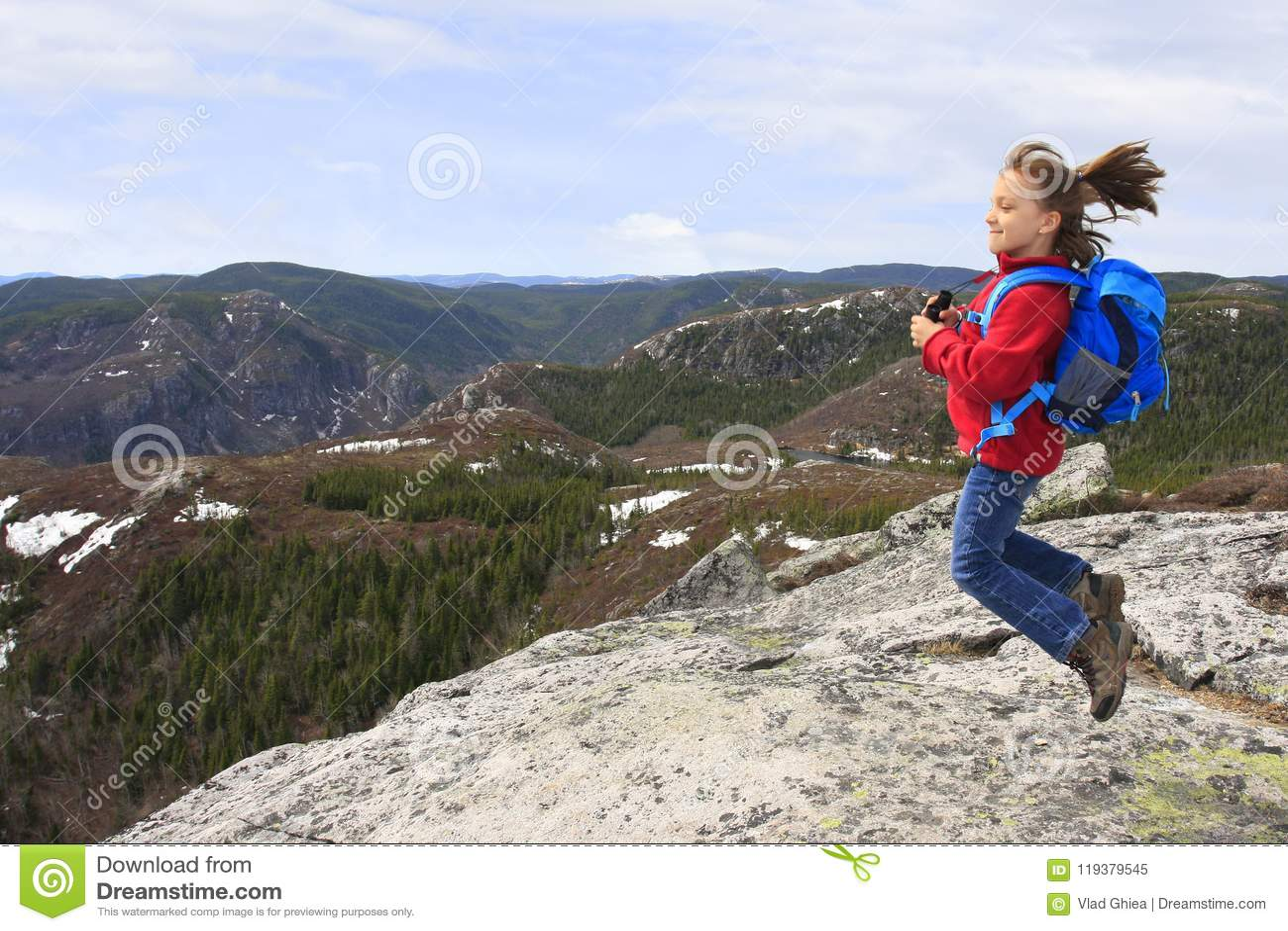 El caminante de la muchacha que salta y que admira las montañas de la belleza ajardina en Quebec