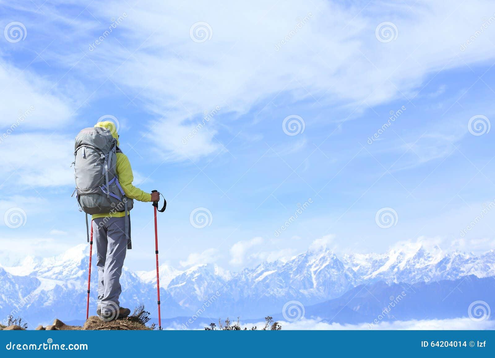 El caminante de la mujer en el balanceo hermoso se nubla el pico de montaña