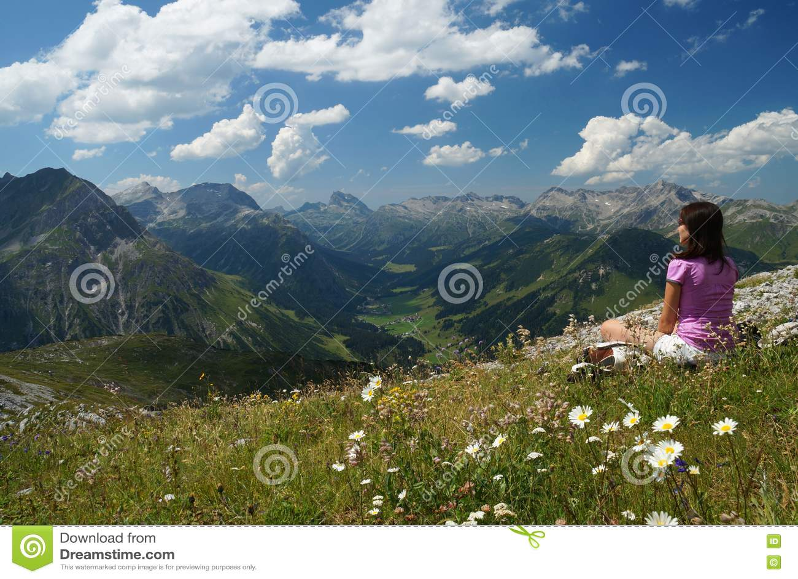 El caminante femenino disfruta de la visión desde un prado alpino en la alta elevación