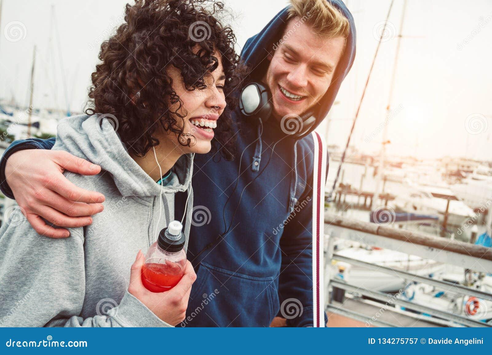 El caminar al aire libre sonriente de los pares jovenes casuales en el puerto