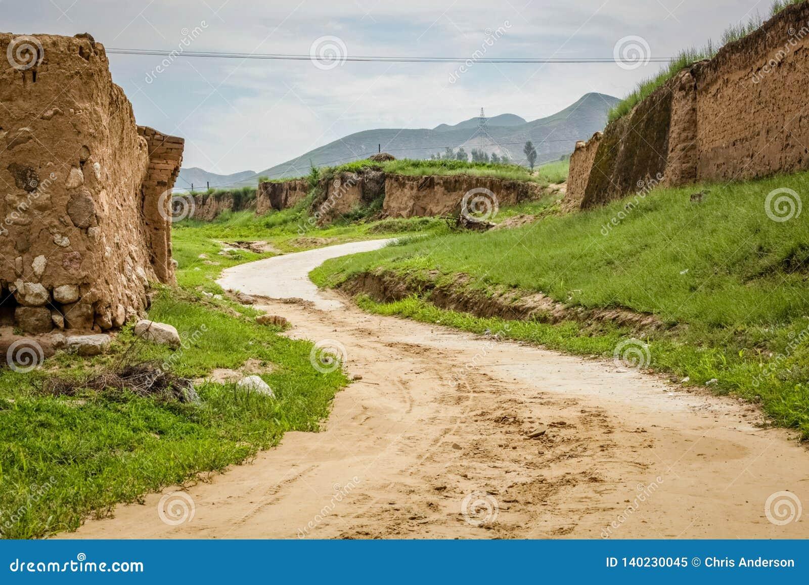 El camino de tierra liso enrolla para arriba una pequeña colina alrededor de una pared del fango en China rural