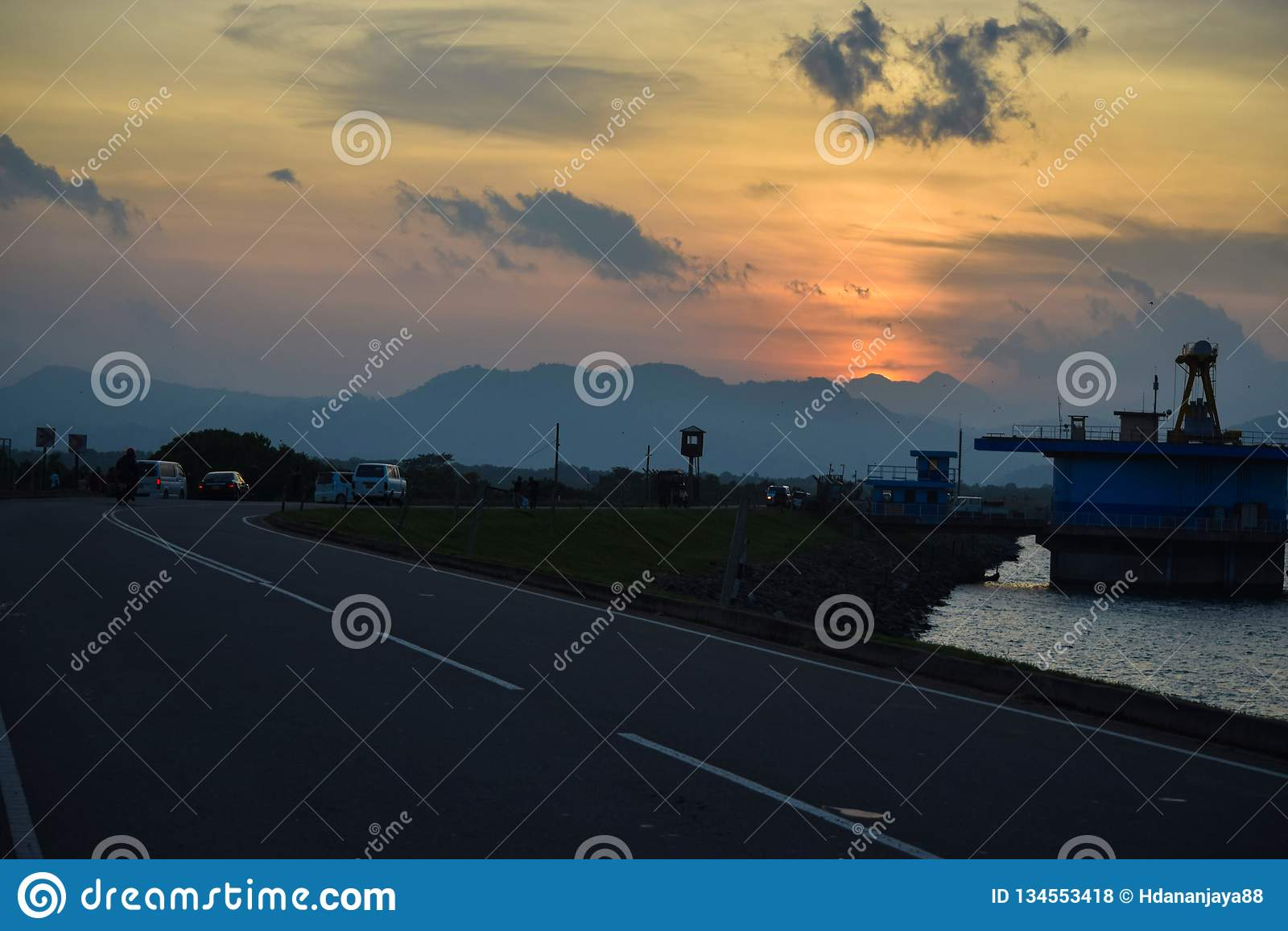 El camino, el río, las montañas y la puesta del sol hermosa