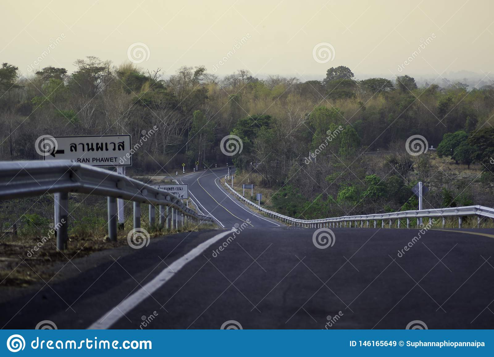El camino tiene una línea amarilla y hay una señal de peligro en el lado izquierdo escarpado abajo de él