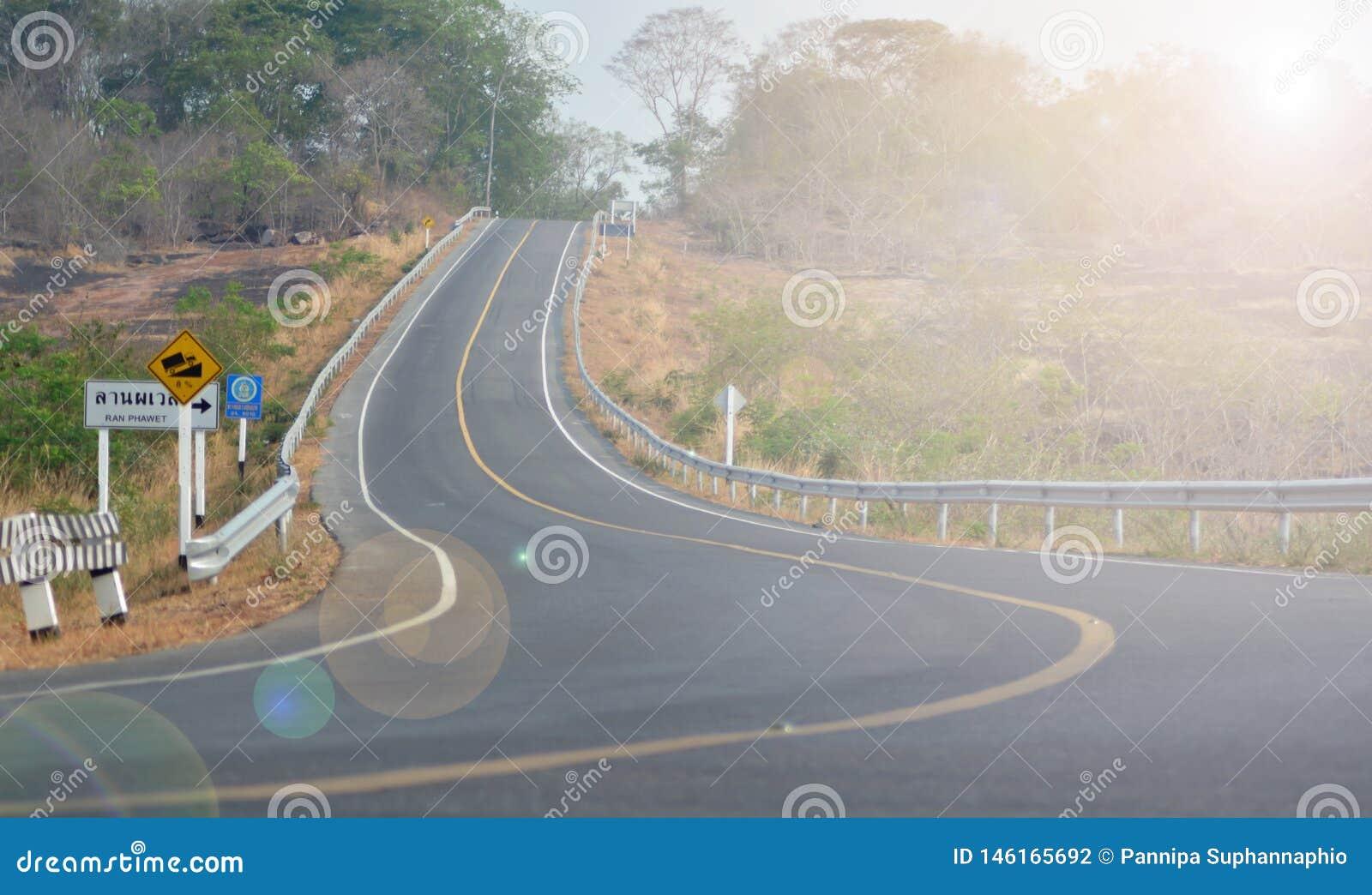 El camino tiene una l?nea amarilla y hay una se?al de peligro en el lado izquierdo escarpado abajo de ?l