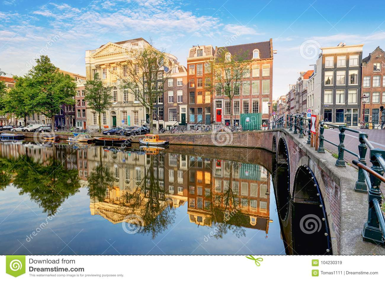 El canal de Amsterdam contiene las reflexiones vibrantes, Países Bajos, panora