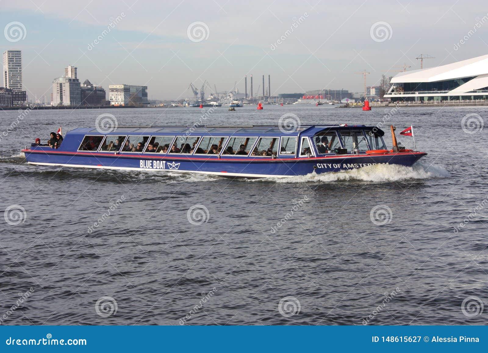 El canal o el r?o delante de la estaci?n central de Amsterdam, usada como transporte p?blico para los viajeros y los turistas