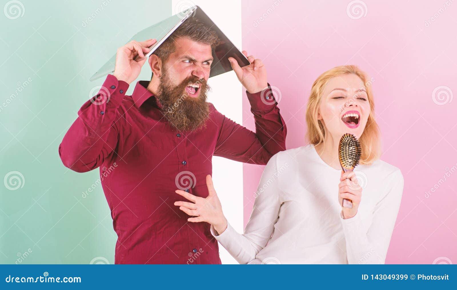 El canto es su pasión La señora canta con el cepillo de pelo como micrófono mientras que el hombre molestó la ocultación debajo d