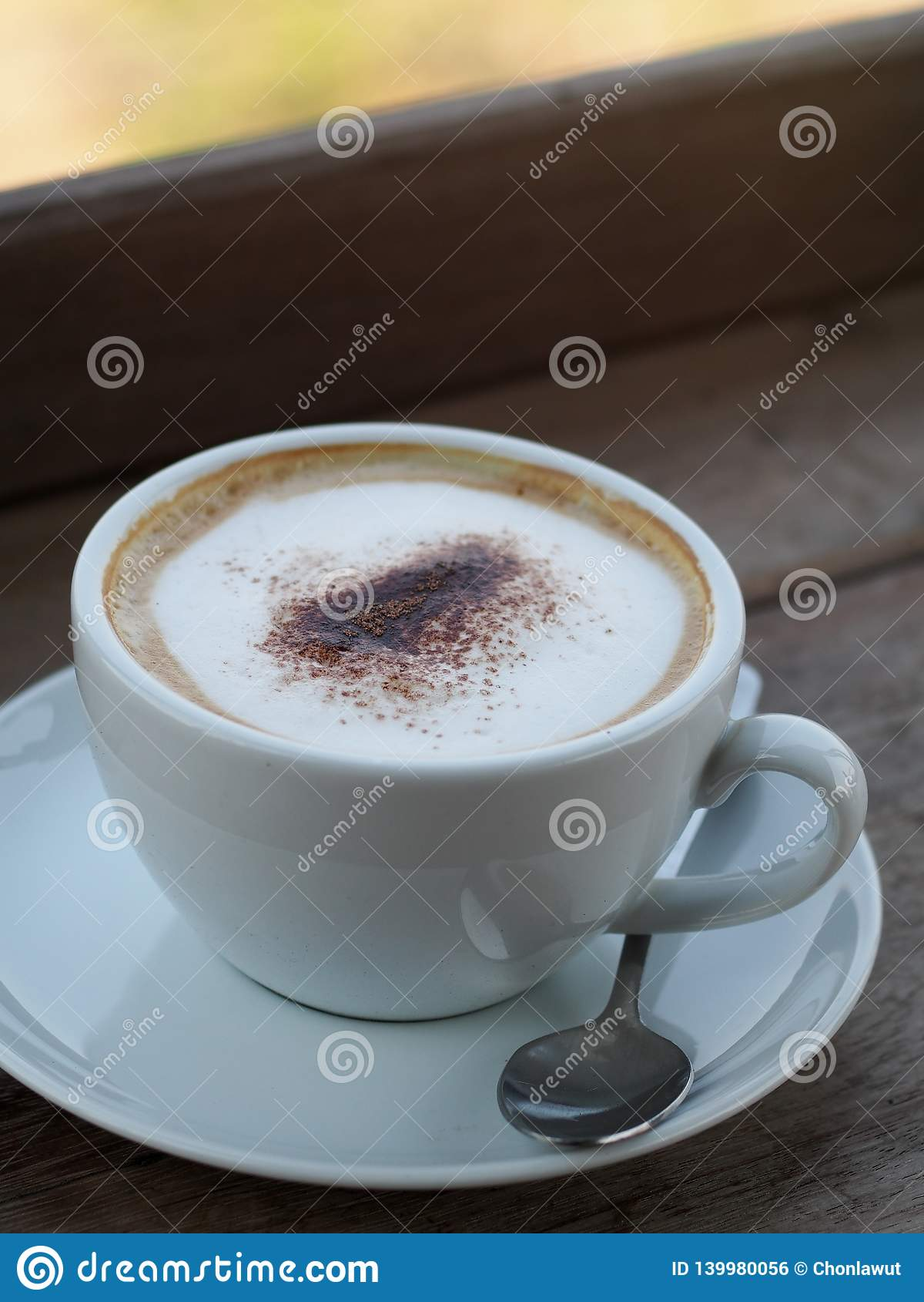El capuchino caliente con la burbuja fina completa poner crema poco polvo de cacao sirvió en la taza de café de cerámica blanca