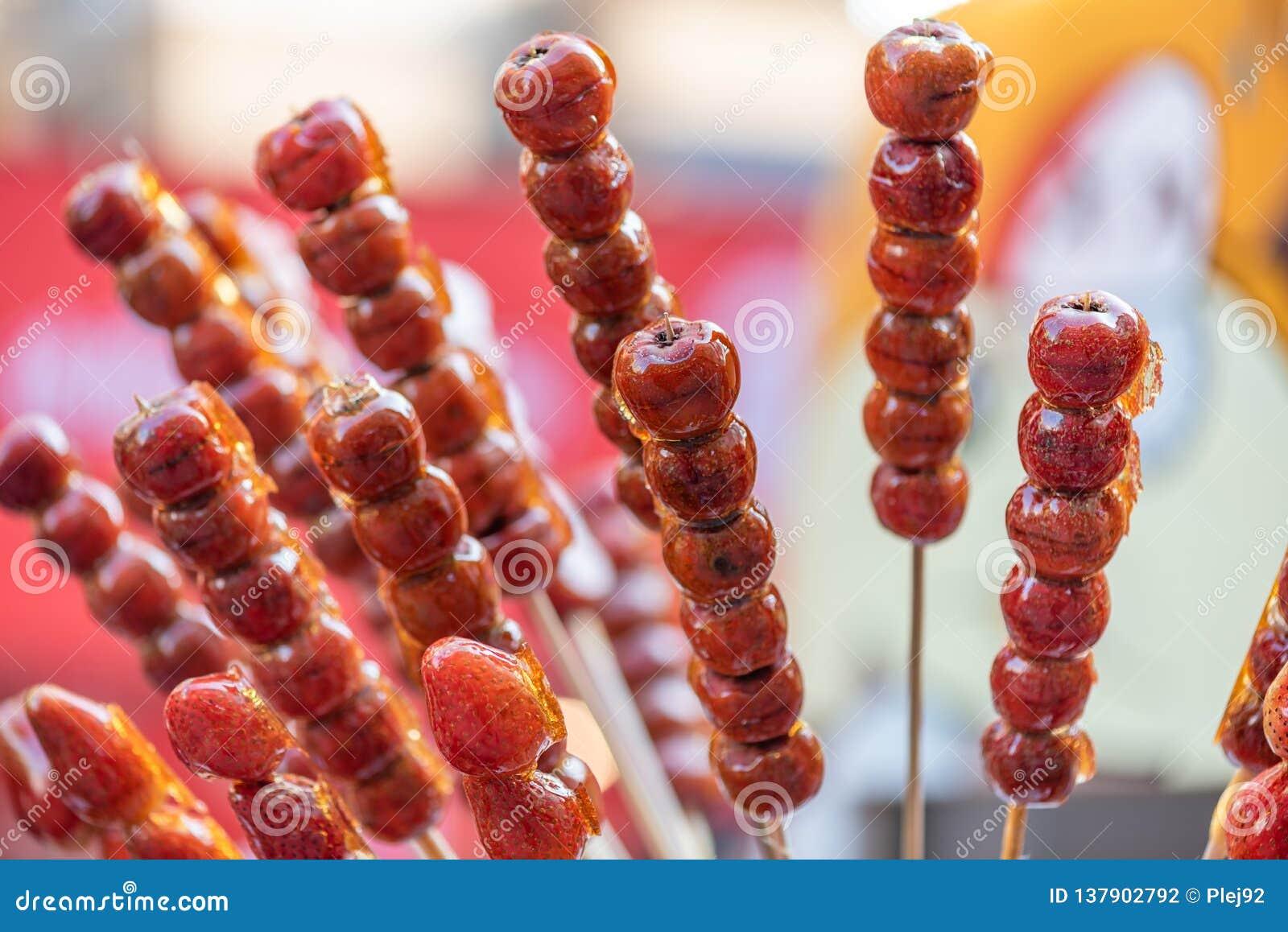 El caramelo duro chino tradicional cubrió los pinchos de la fruta