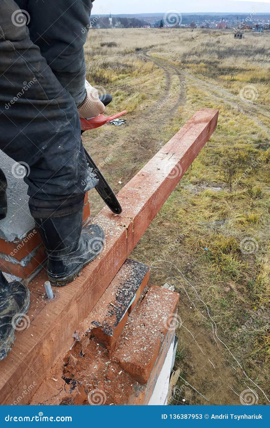 El carpintero con una motosierra hace bebió en una construcción del haz de madera de casas