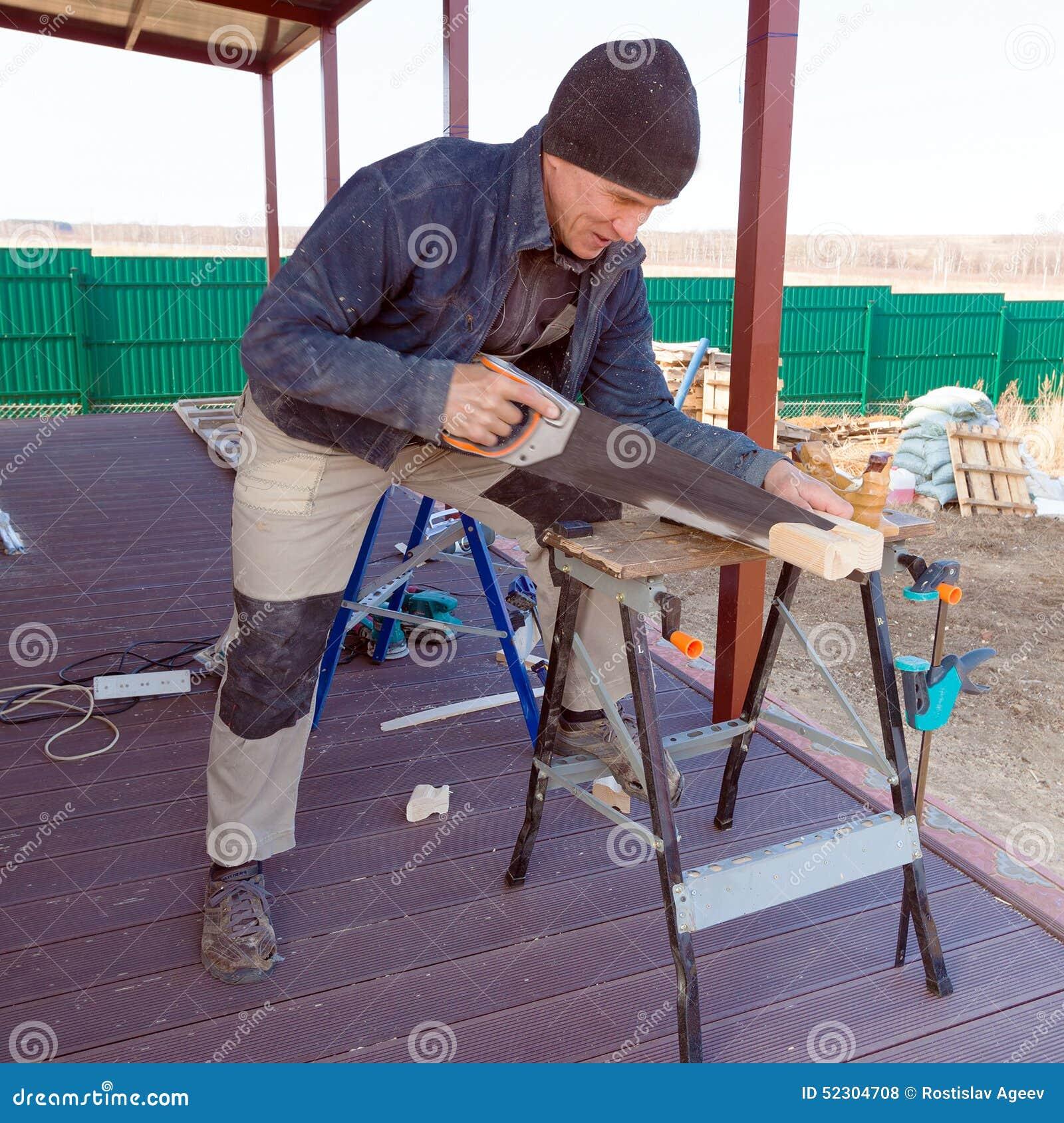 El carpintero con vio al aire libre