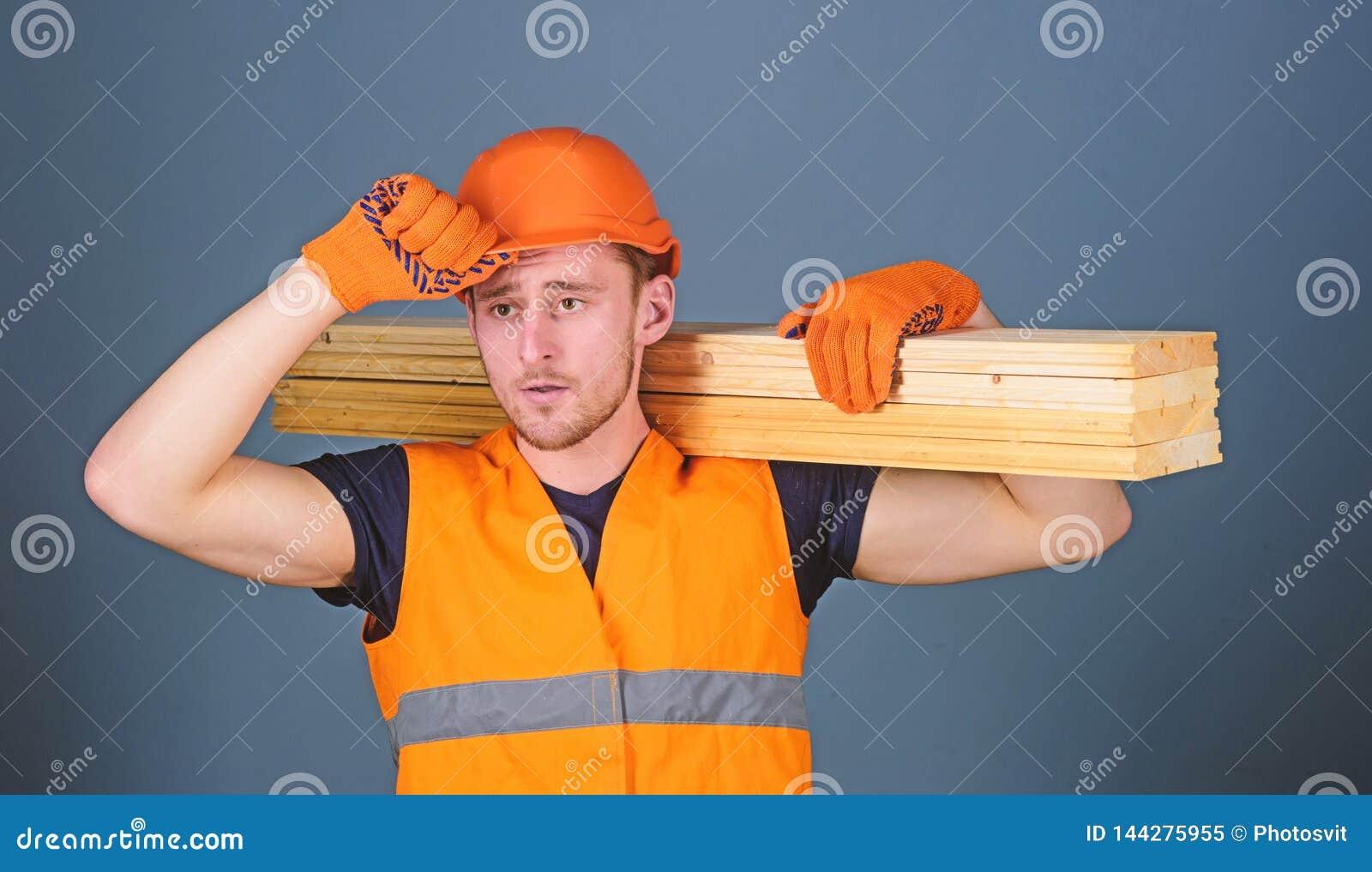 El carpintero, carpintero, constructor fuerte en cara seria lleva el haz de madera en hombro Hombre en el casco, casco y