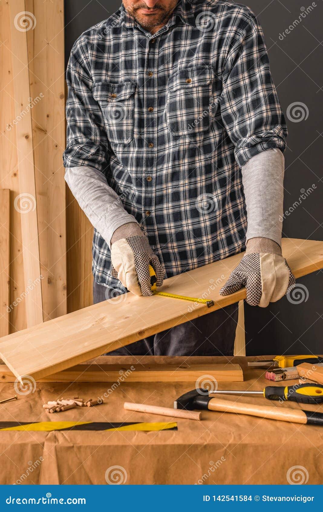 El carpintero está midiendo el tablón de madera de pino