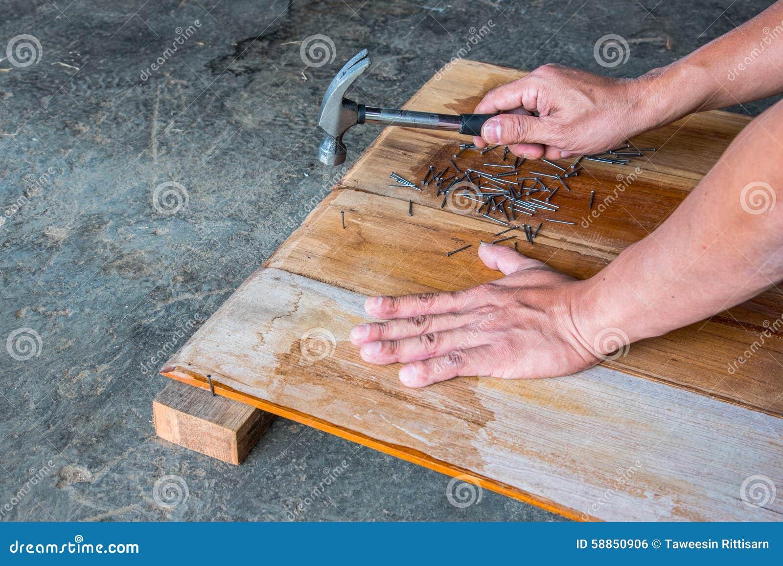 el carpintero que clava al tablero de madera para hacer los muebles foto de archivo