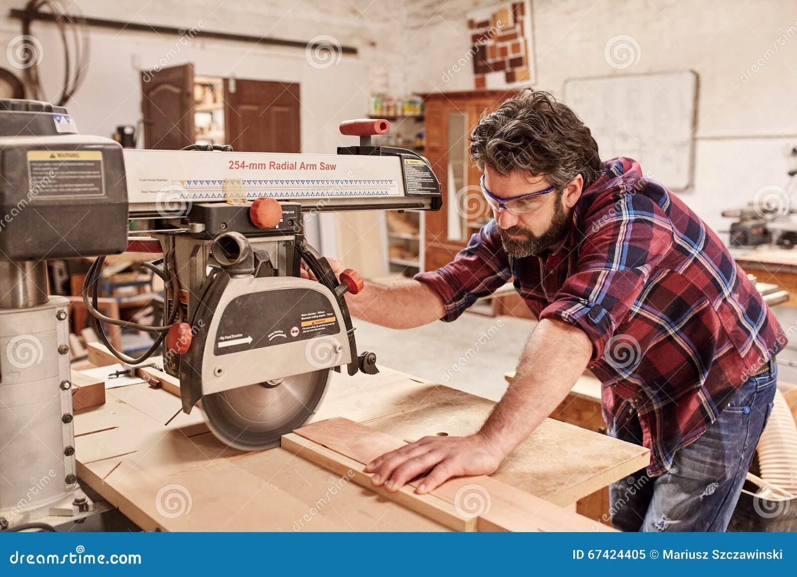 El carpintero que usaba el brazo radial vio para cortar la for Cortar madera con radial