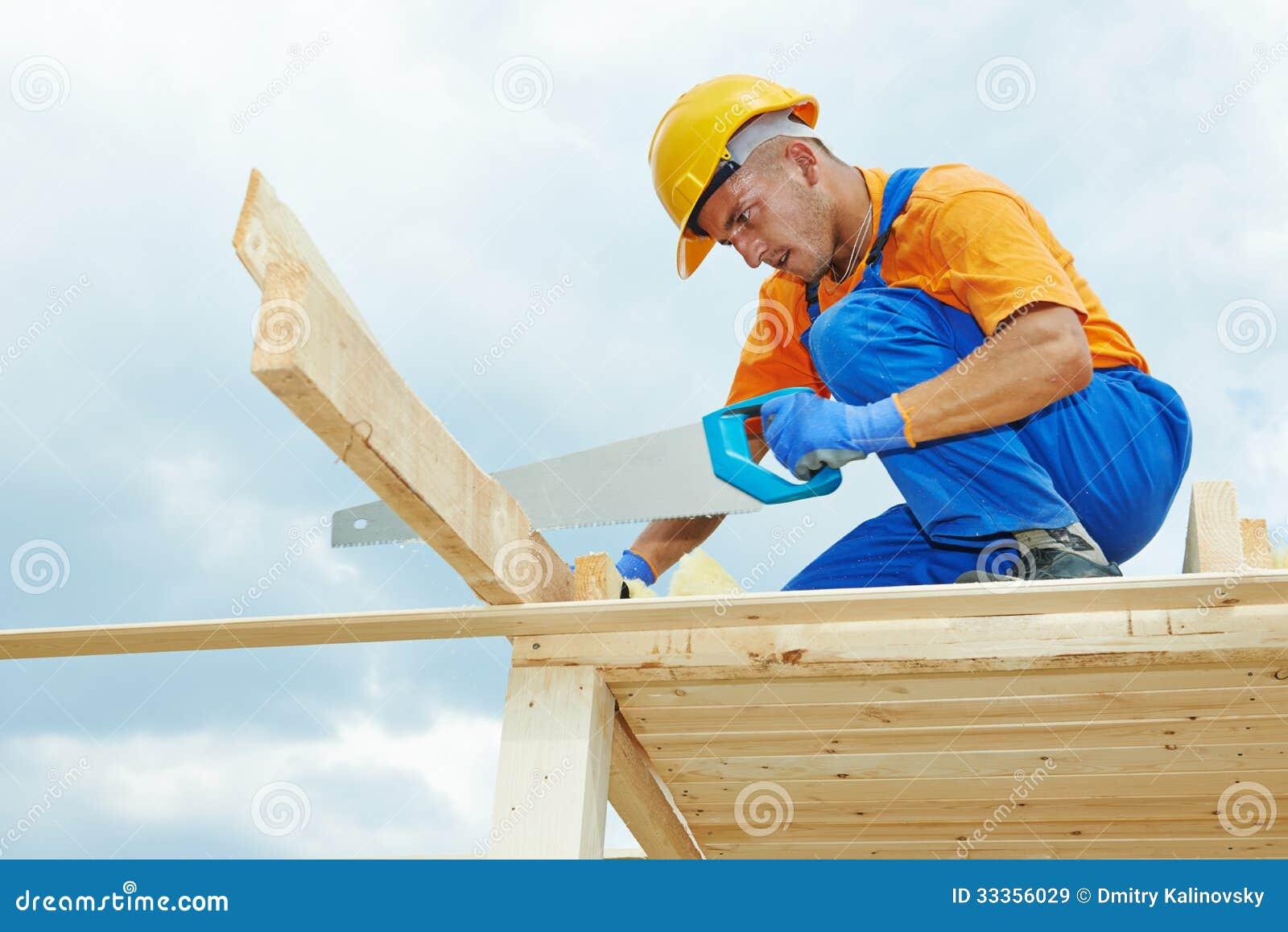El carpintero trabaja con la sierra de la mano