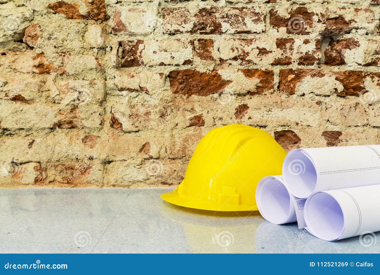El casco de seguridad y los dibujos proyectan en fondo de la pared de ladrillo