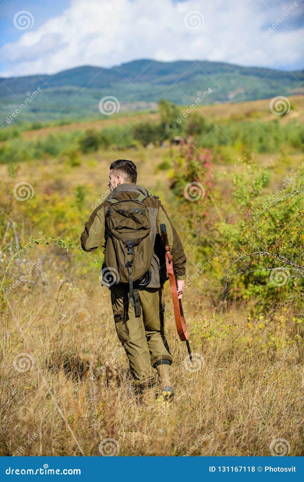 El cazador del hombre lleva el fondo de la naturaleza del rifle La experiencia y la práctica presta la caza del éxito Temporada d