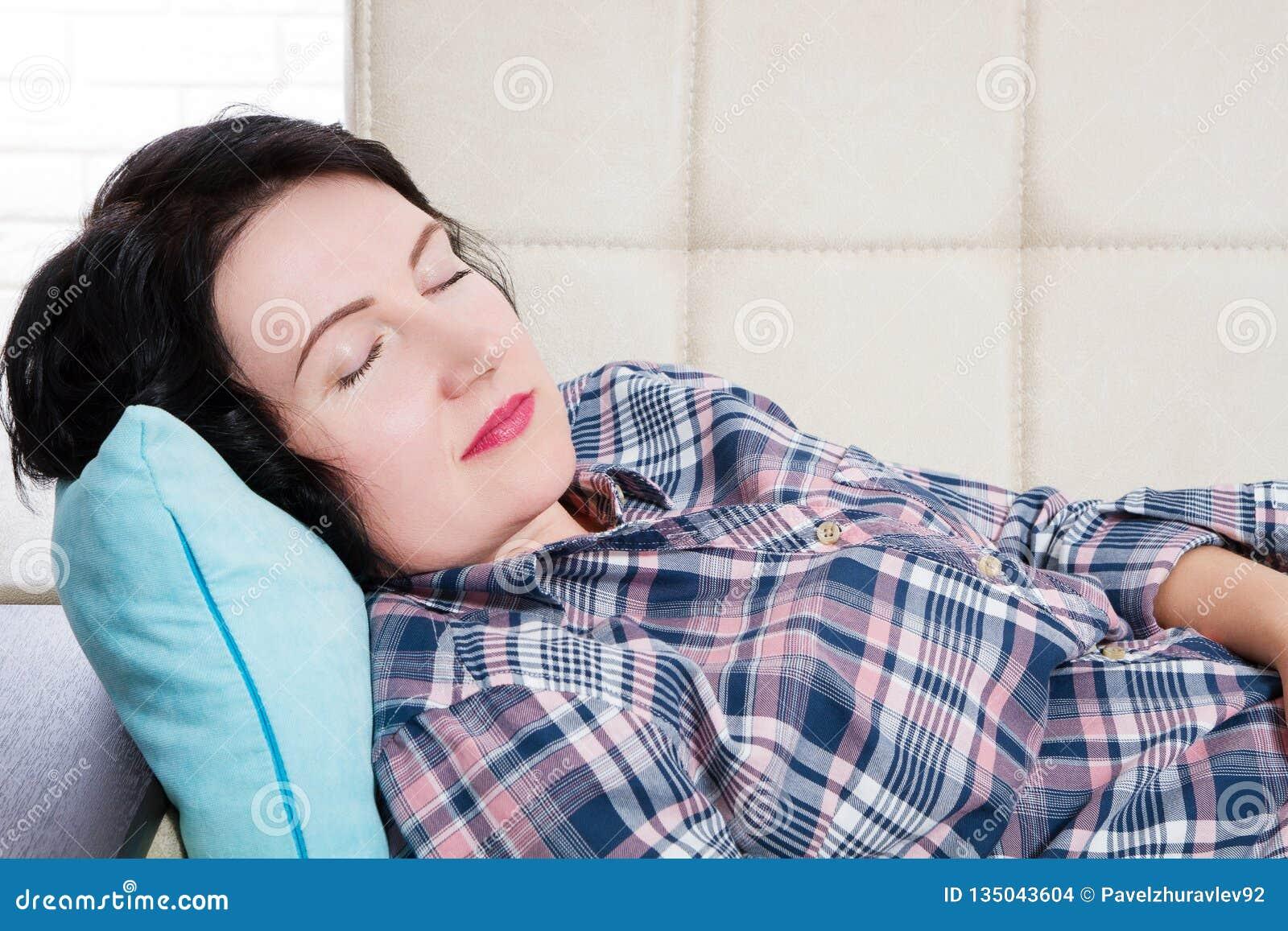 El centro envejeció a la mujer hermosa que mentía en el sofá que dormía en casa después del día laborable duro cansado Sueños dul