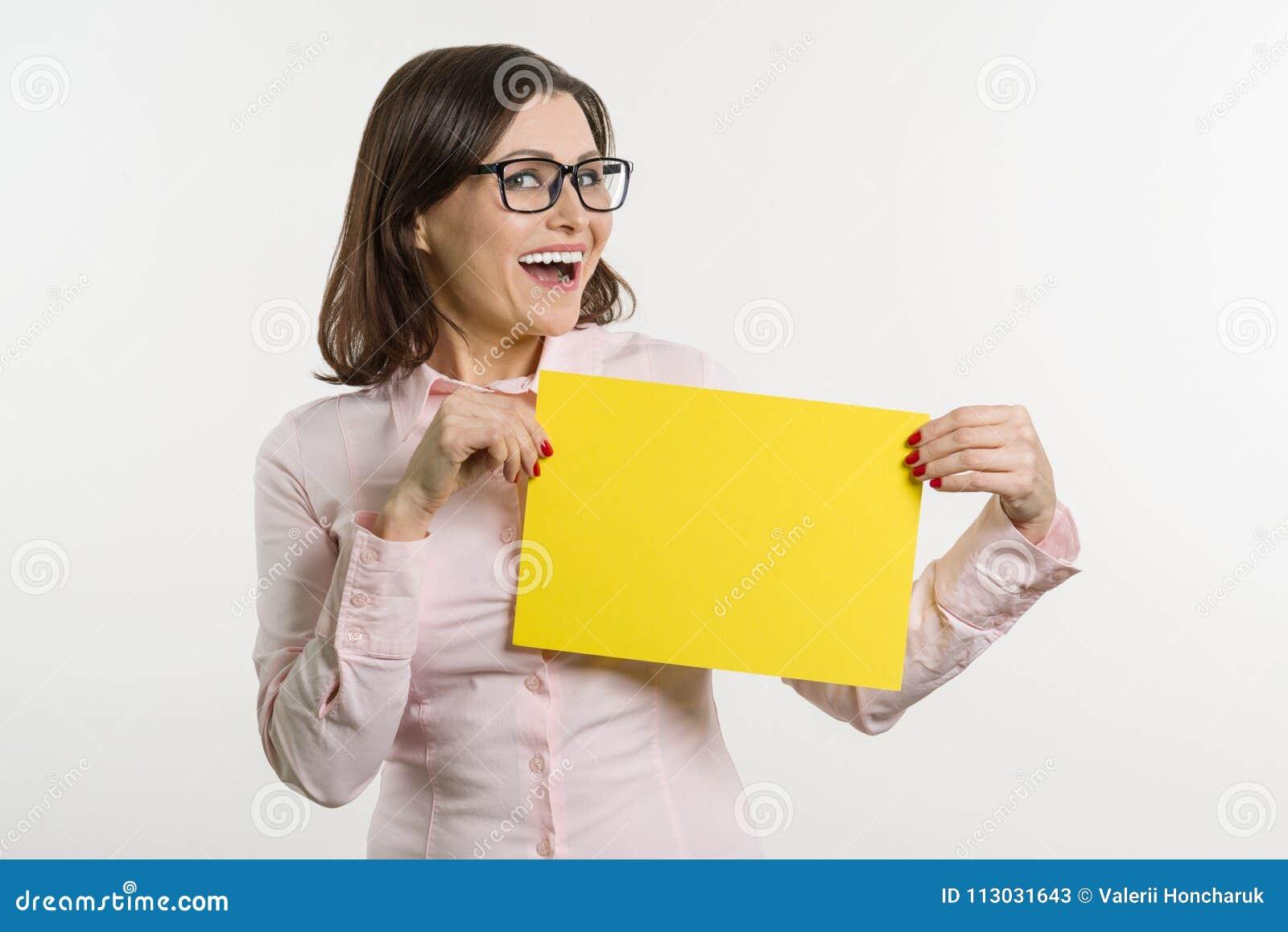 El centro sonriente envejeció a la mujer con la hoja de papel amarilla en el fondo blanco