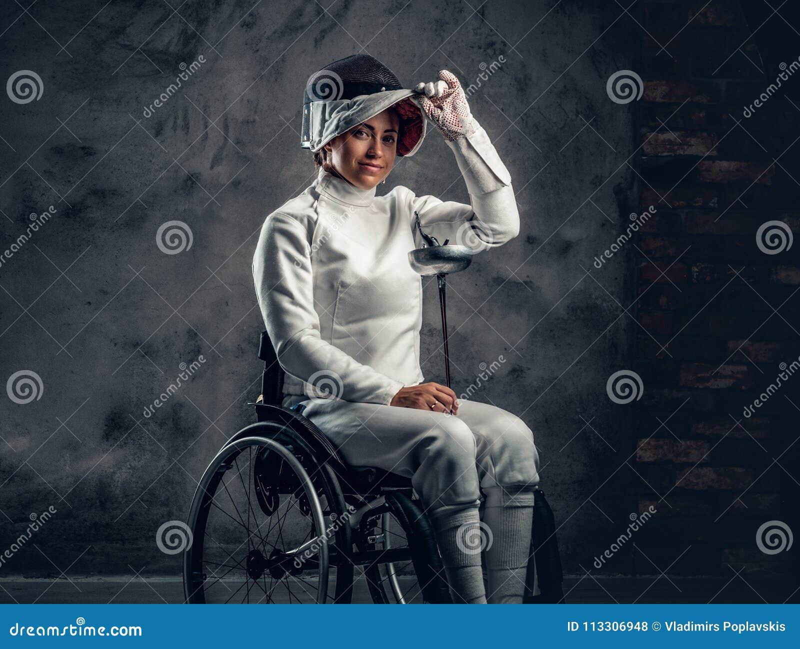 El cercador de sexo femenino en silla de ruedas sostiene la máscara de la seguridad y una espada