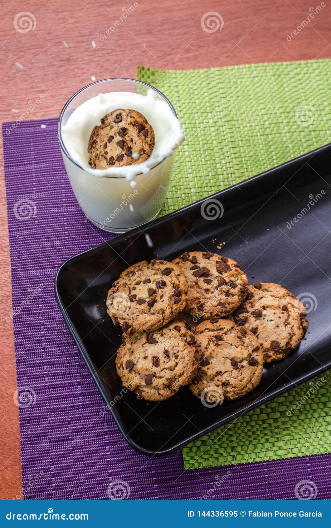El chapoteo de la leche causó por la galleta con las chispas del chocolate que caían