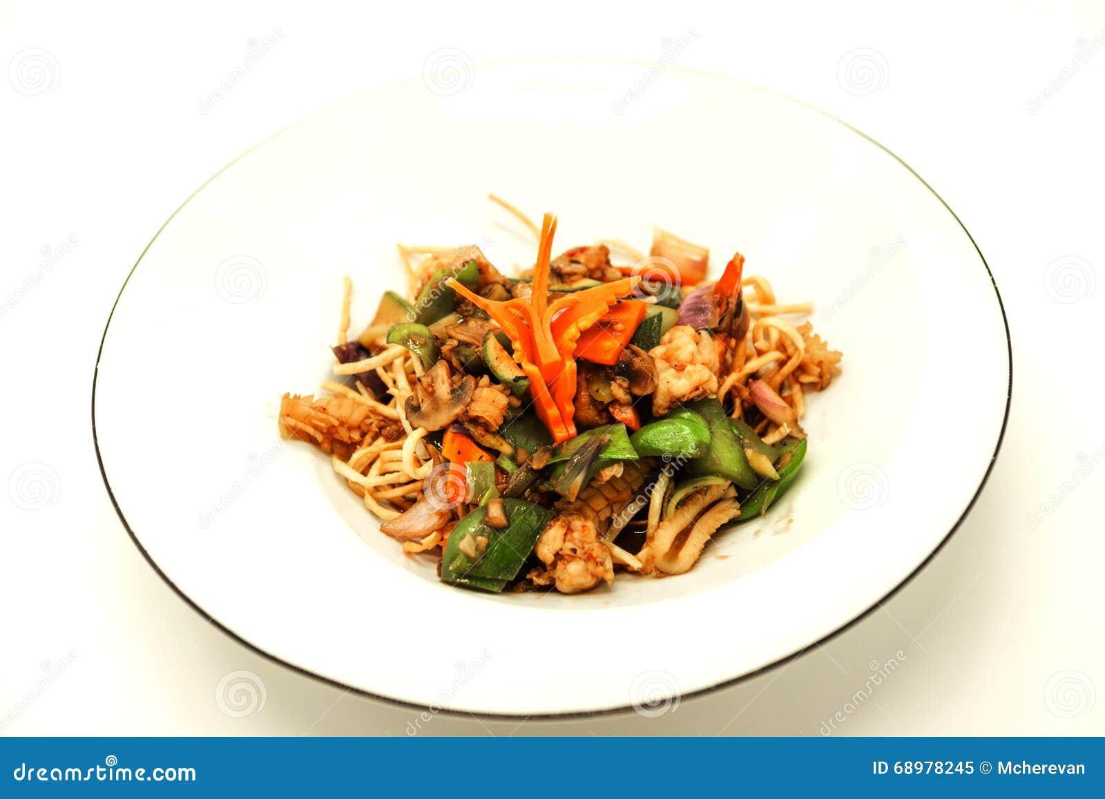El chino frió los tallarines con calamares, un pulpo y las verduras