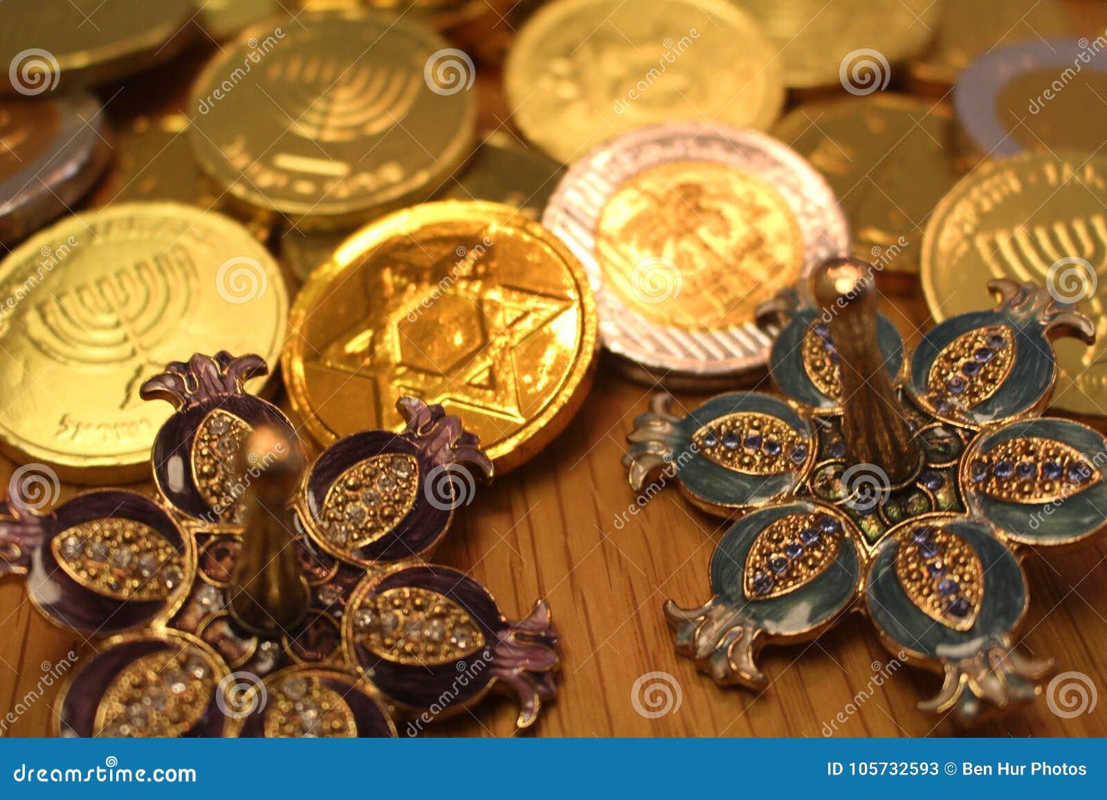 El chocolate del gelt de Jánuca acuña con el dreidel trasero y de plata de la estrella de David encendido con la granada