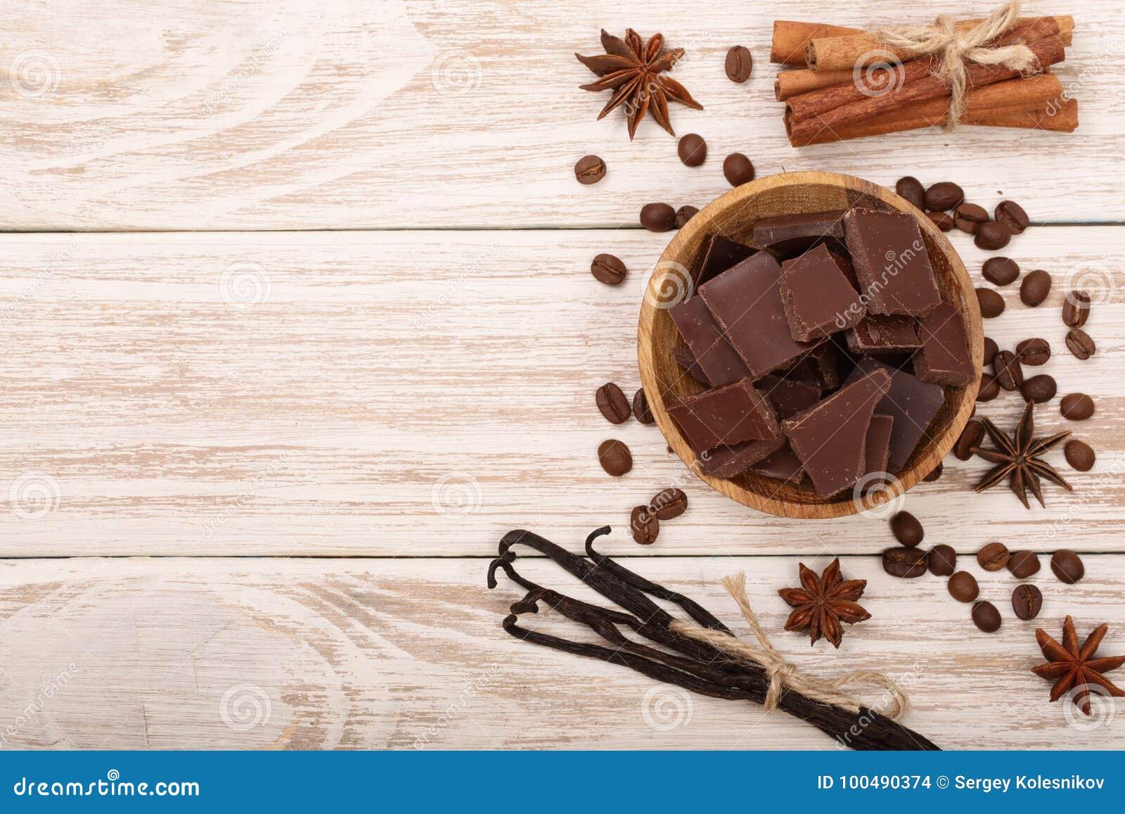 El chocolate, vainilla se pega, el canela, granos de café en el fondo de madera blanco con el espacio de la copia para su texto V